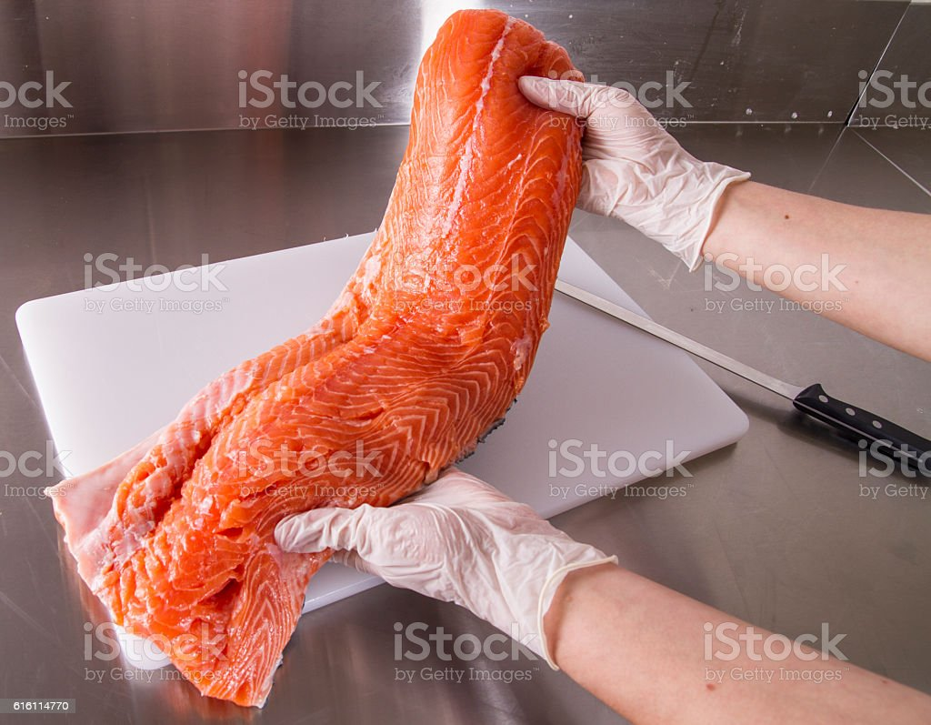 Cook cut up raw fish in kitchen stock photo