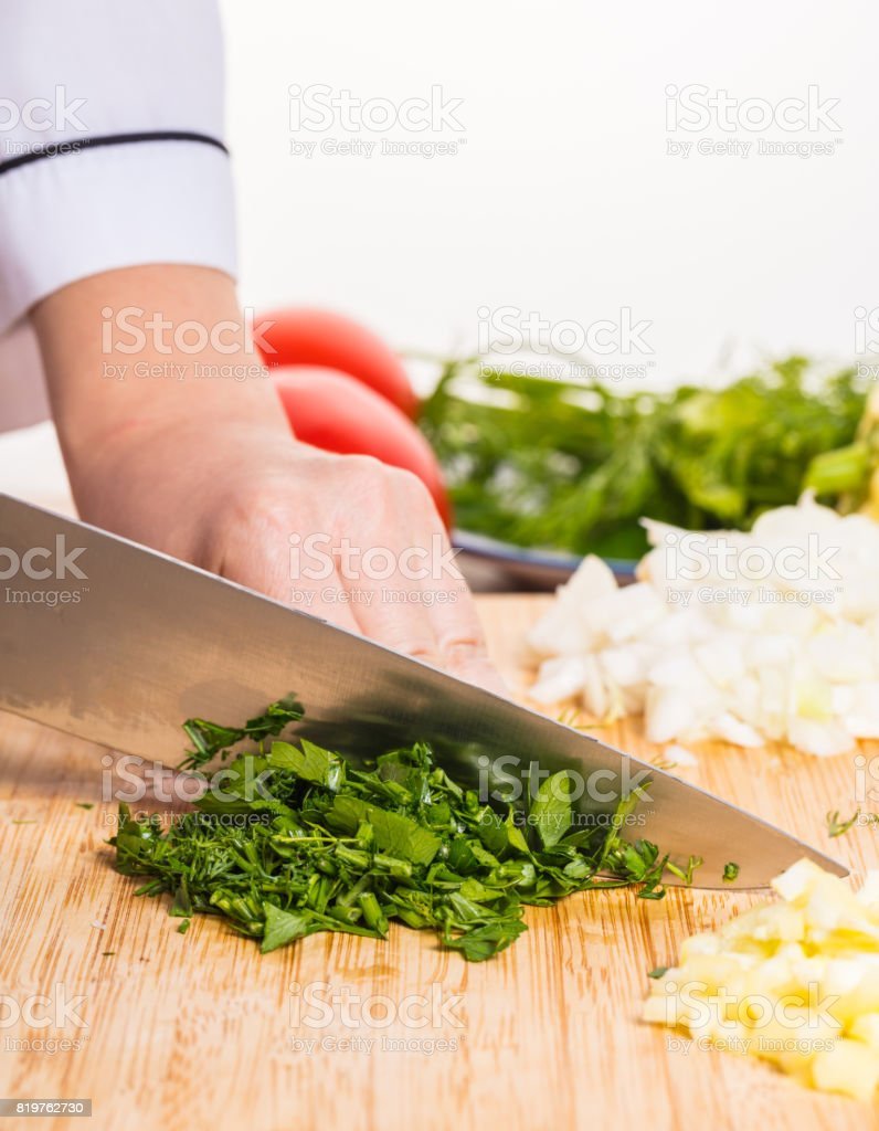 Cook cuts greens with a knife stock photo