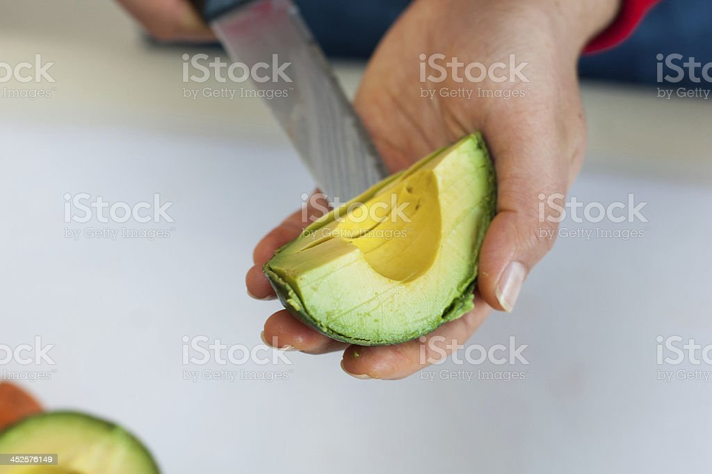 Cook cutting and preparing an avocado royalty-free stock photo