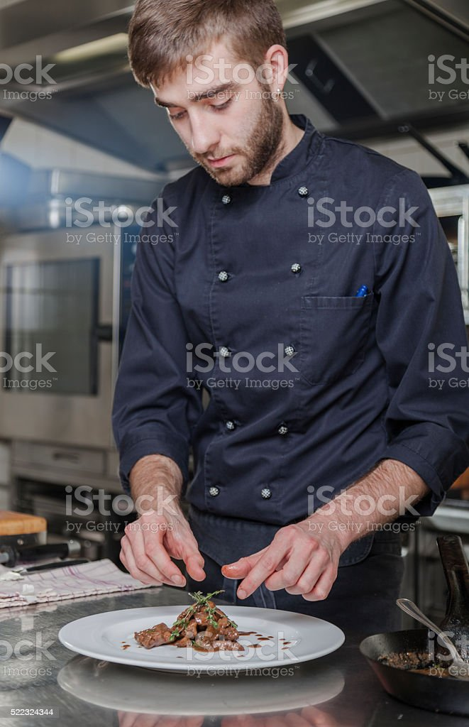 Cook decorates duck liver in the kitchen stock photo