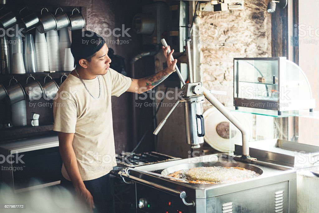 Cook frying Mexican Churros stock photo