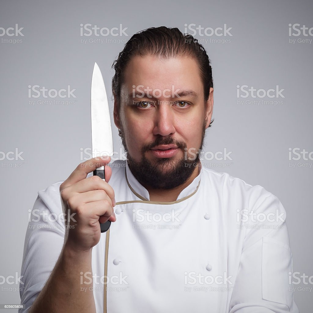 Cook holding a sharp knife. stock photo