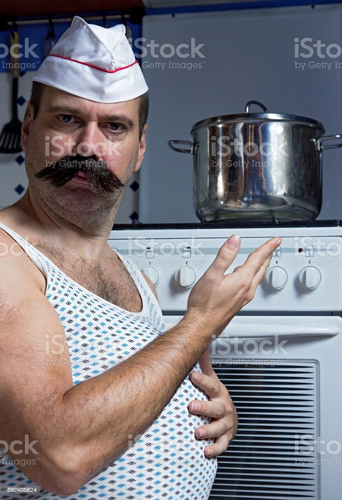 cook in the kitchen shows at pot stock photo
