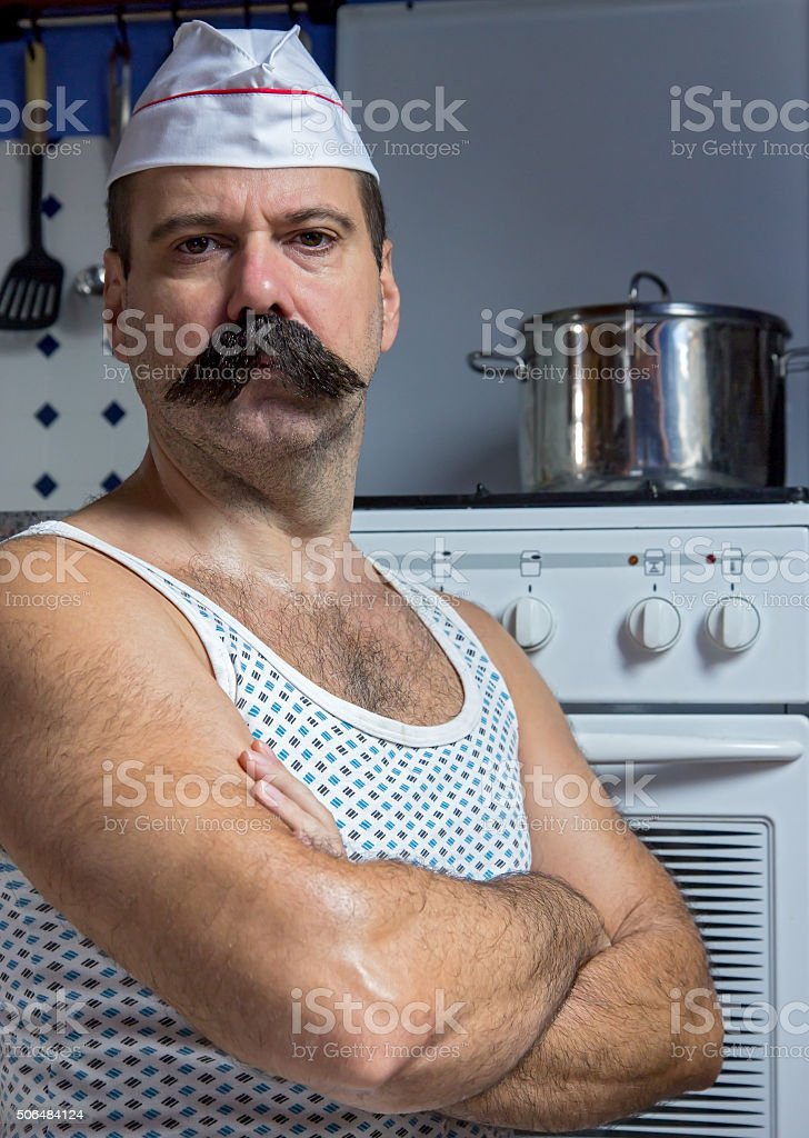 cook in undershirt standing in the kitchen stock photo