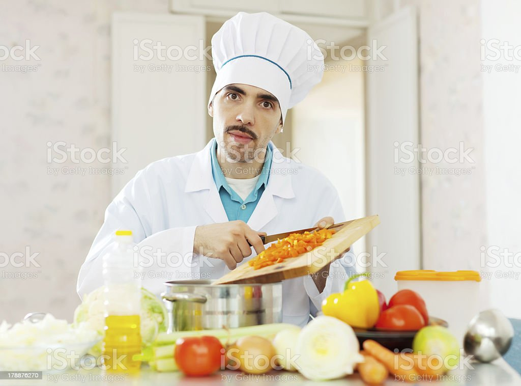 cook in uniform works with vegetables royalty-free stock photo