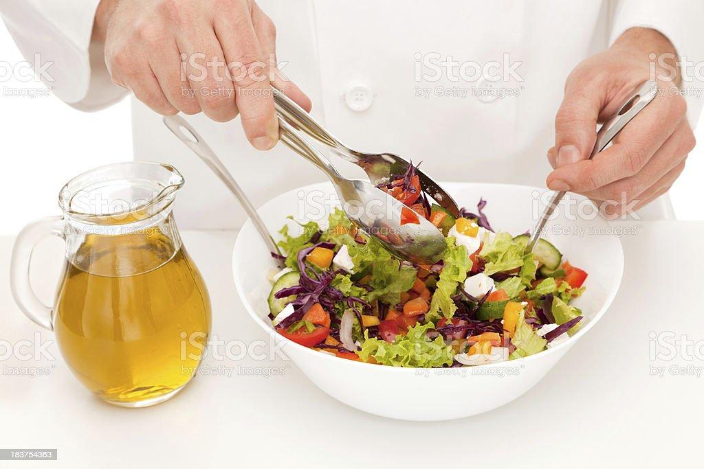 Cook in white uniform preparing salad royalty-free stock photo