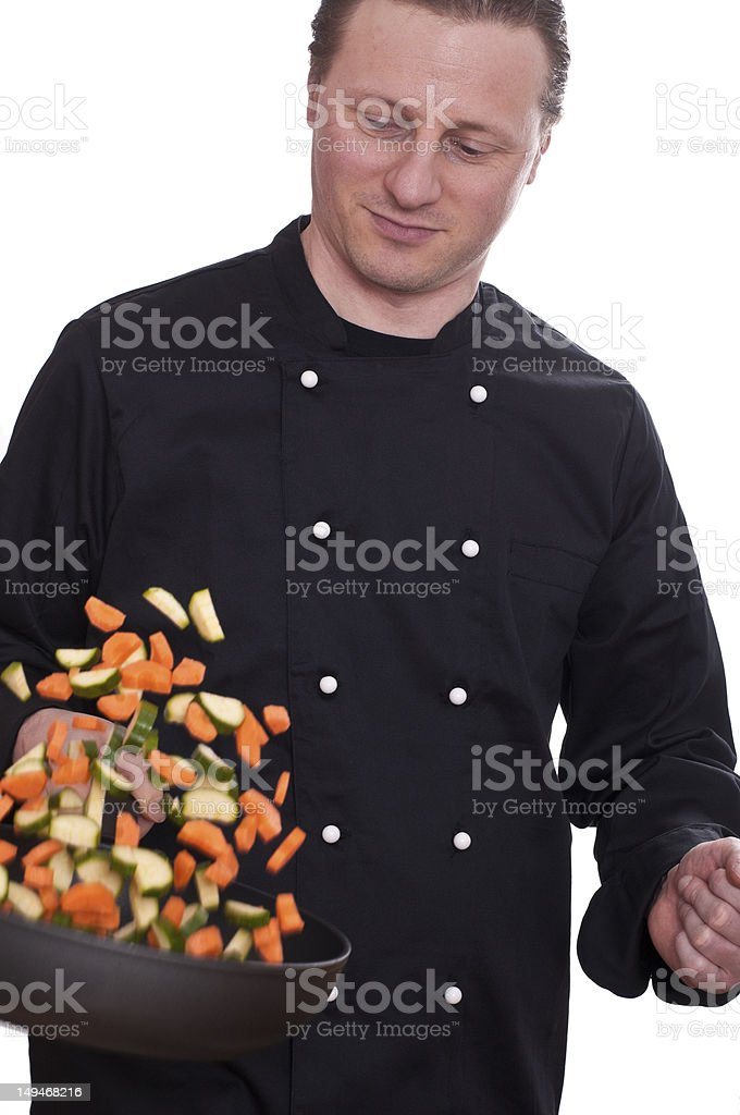 Cook is turning the vegetables in a pan royalty-free stock photo