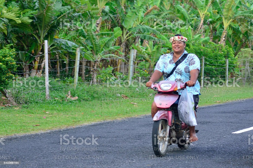 Cook Islander woman rides a motorbike stock photo
