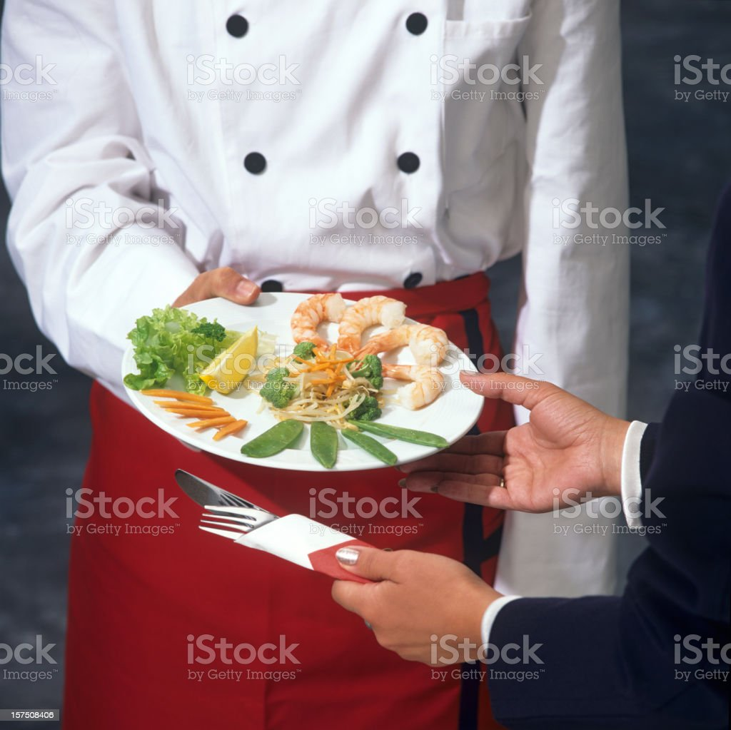 Cook offering a fish vegetable plate to woman royalty-free stock photo