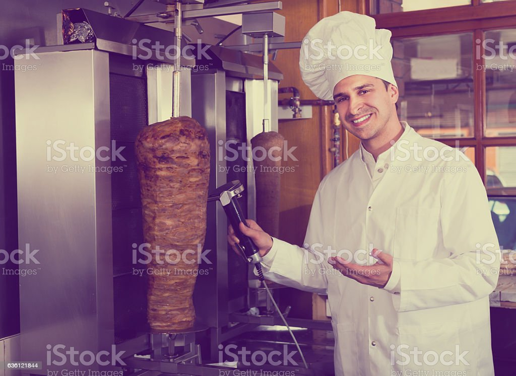 Cook posing near meat for kebab stock photo