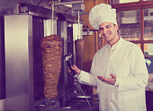 Cook posing near meat for kebab