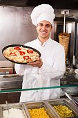 Cook posing with Italian pizza