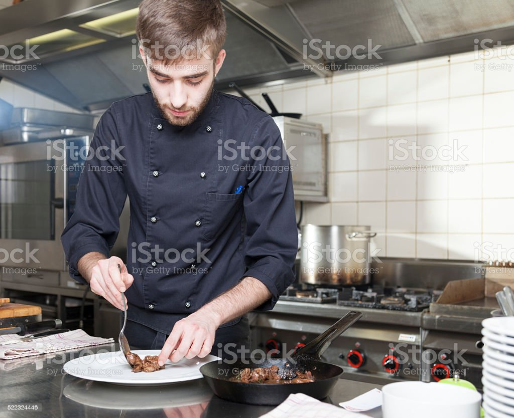 Cook prepares duck liver on a white plate stock photo