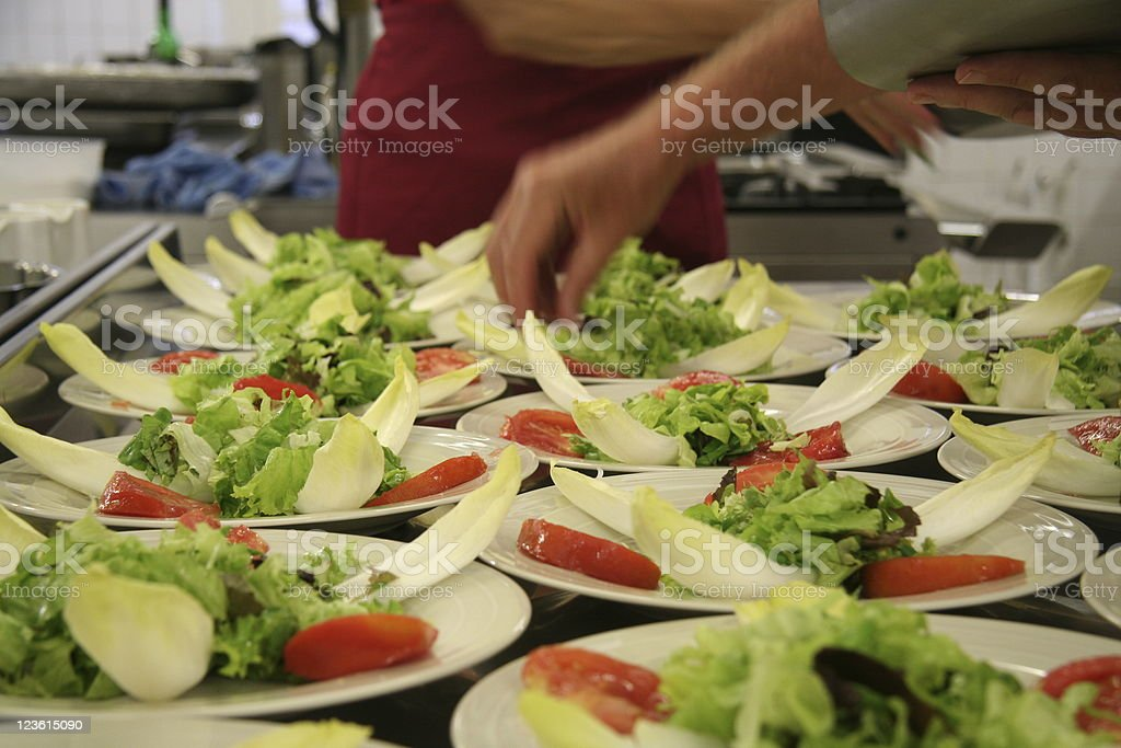 cook preparing dishes of salad stock photo