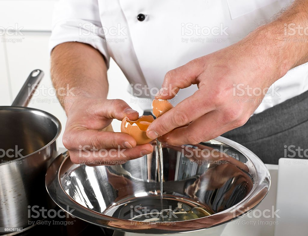cook separating yolk from egg royalty-free stock photo