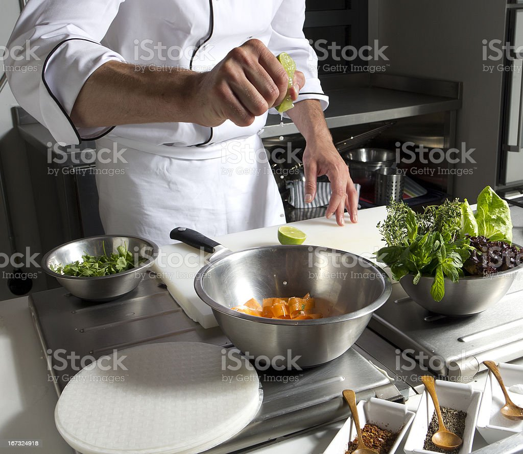 cook squeezing lemon on vegetable in cooking pot royalty-free stock photo