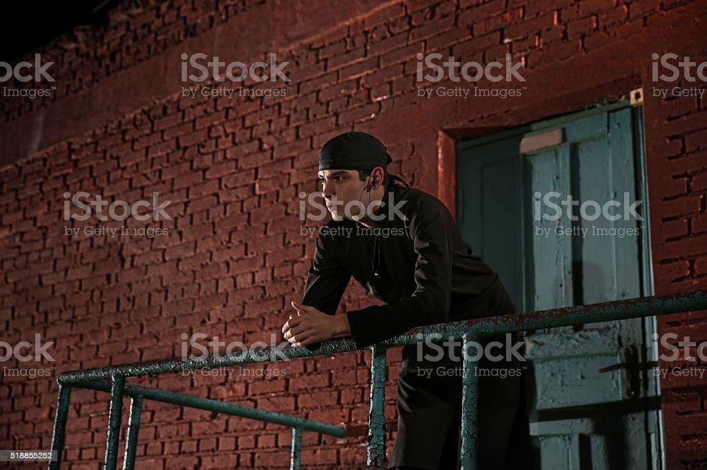 Cook standing near kitchen backdoor listening to music in headphones stock photo