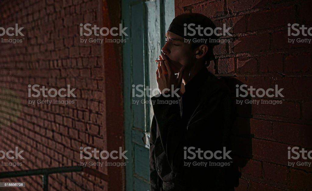 Cook standing near kitchen backdoor smoking stock photo