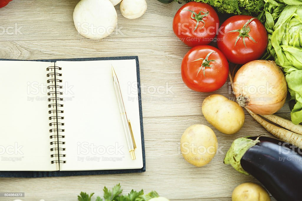 Cookbook and vegetables, directly above shot stock photo