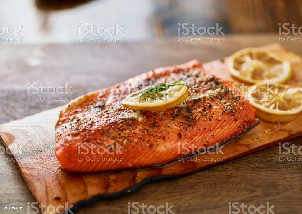 cooked cedar planked salmon with lemon and dill stock photo