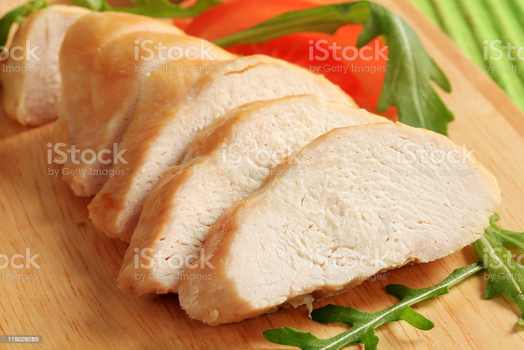Cooked chicken beast fillet with green vegetables garnish stock photo