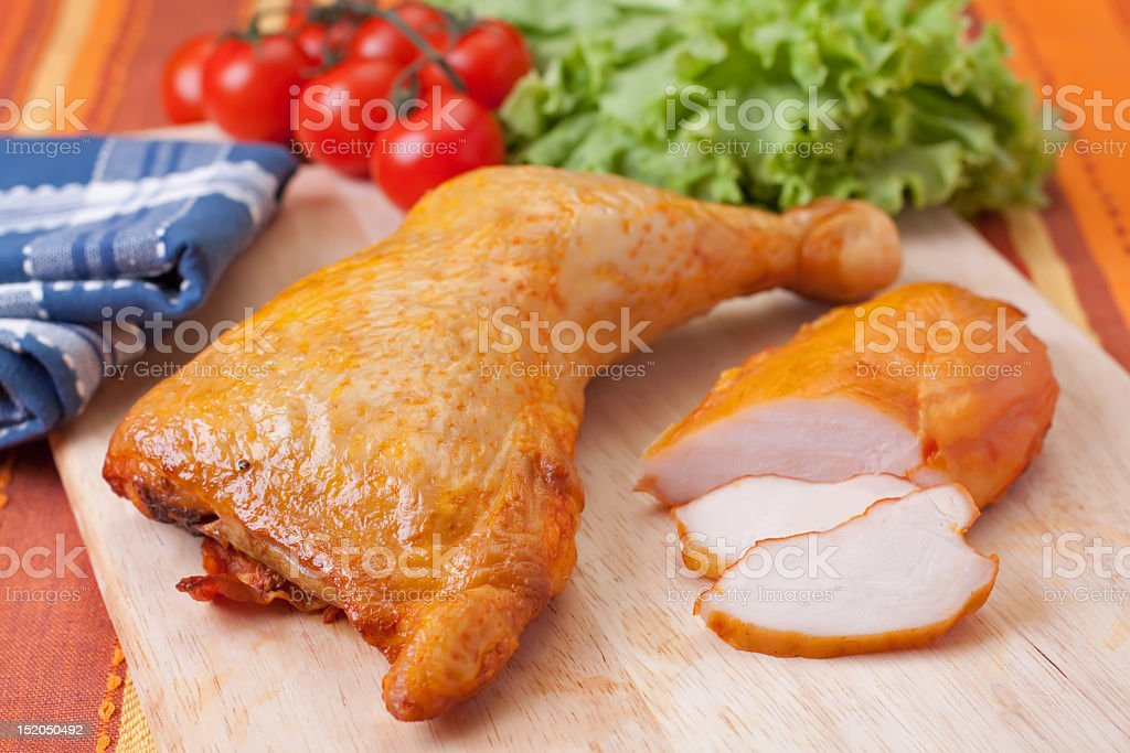 Cooked chicken leg next to chicken slices and tomatoes stock photo