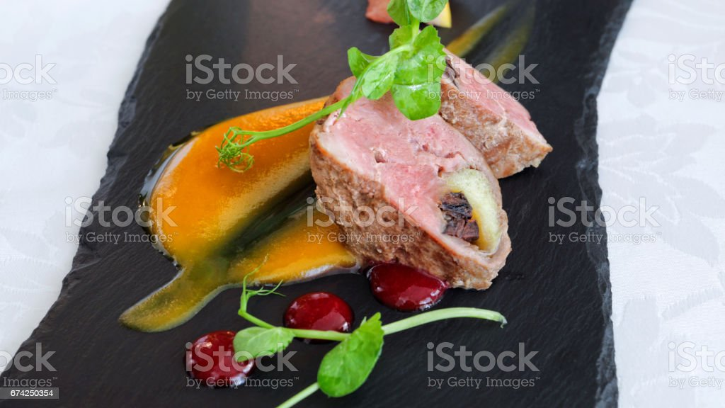 Cooked cuts of pork meat served with red cranberry and orange sauce, on a black stone slate plate . stock photo