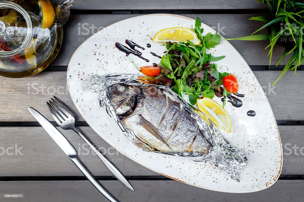 cooked fish on white plate in restaurant at wooden table stock photo