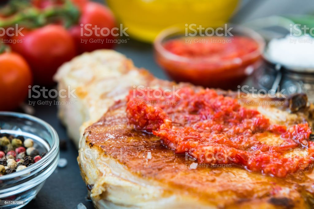 Cooked meat with red sauce, garlic, cherry tomatoes, olive oil stock photo
