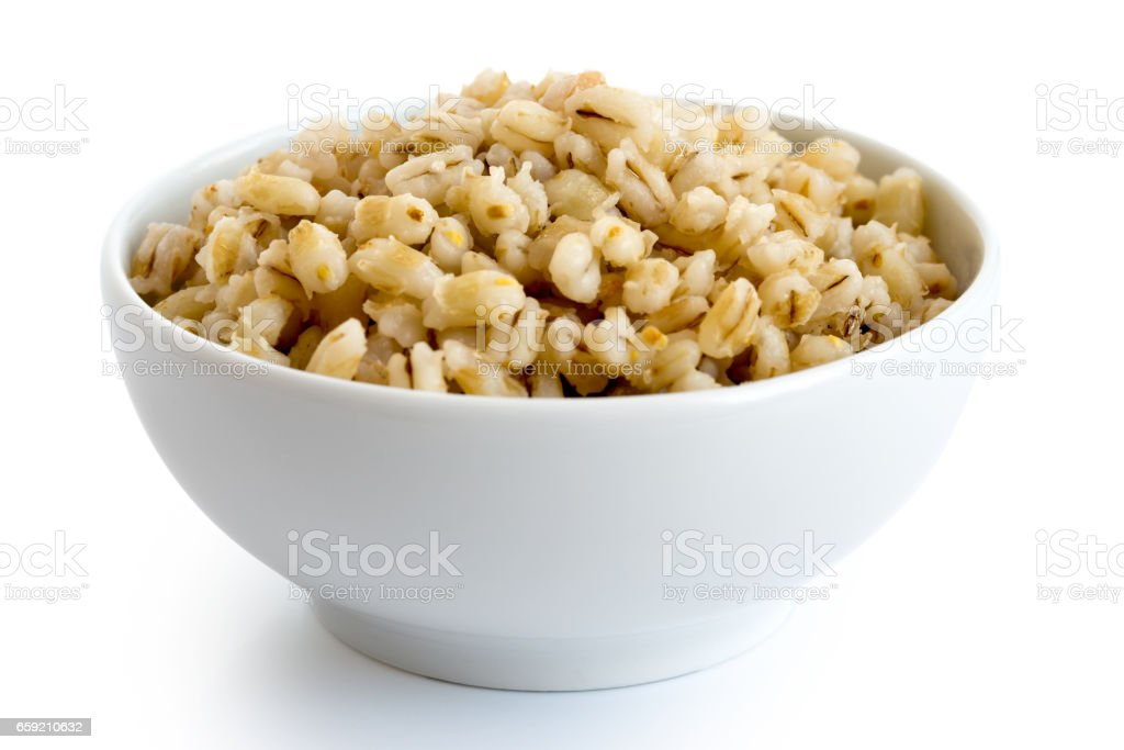 Cooked pearl barley in white ceramic bowl isolated on white. stock photo