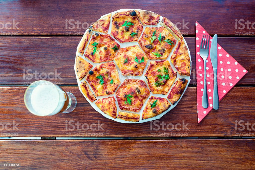 Cooked Pizza in Shape of Soccer Ball with Beer Glass stock photo