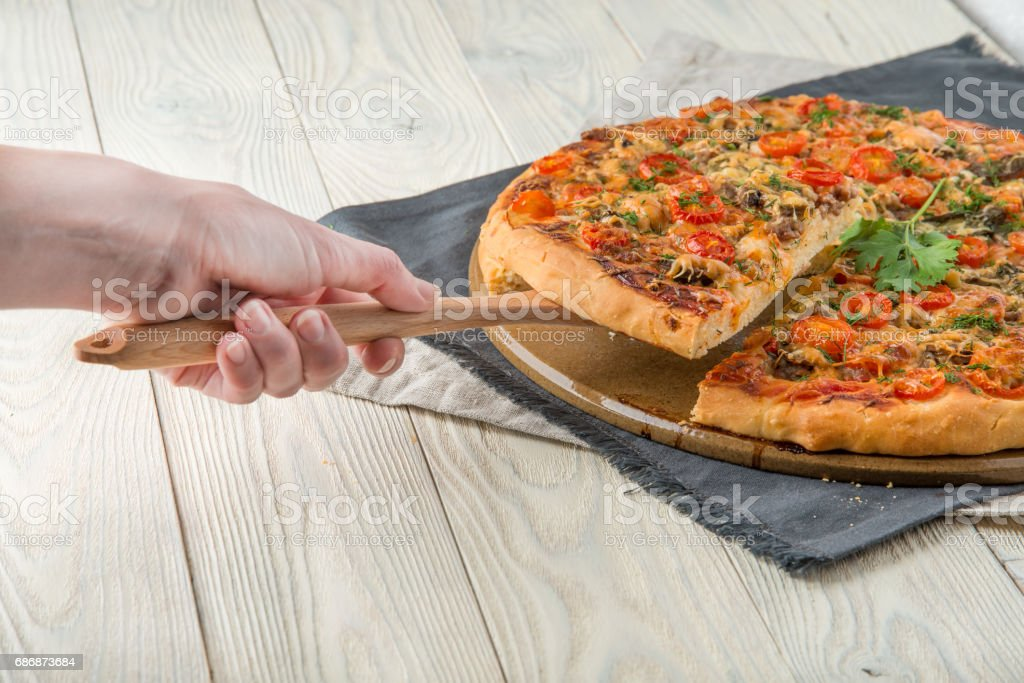 cooked pizza on a wooden background top view stock photo