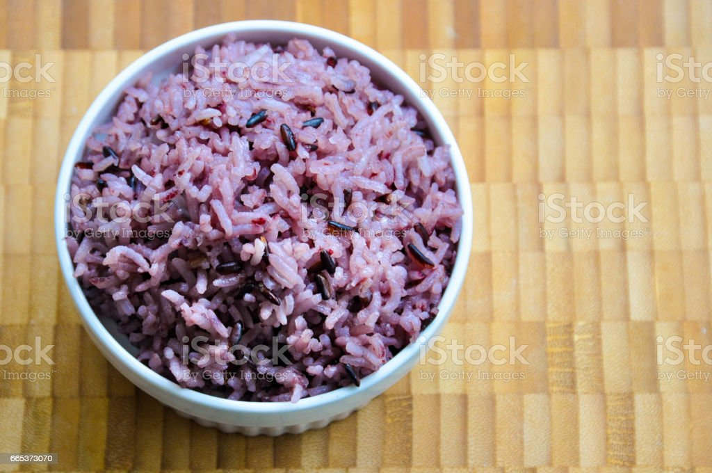 Cooked purple rice berry in white bowl on wood plate. stock photo