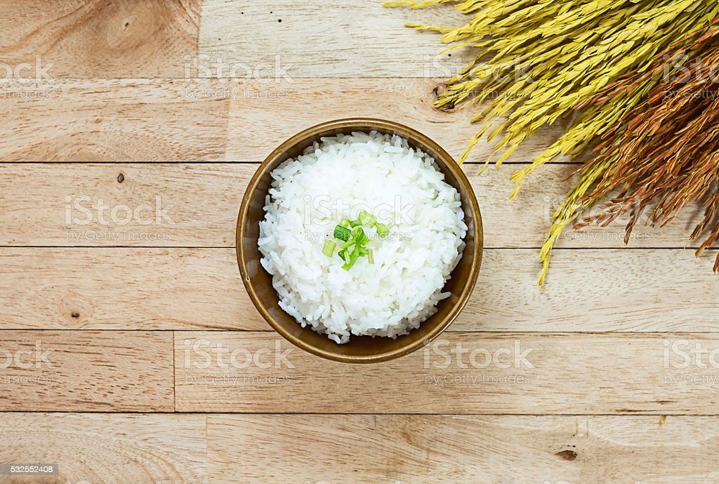 Cooked rice and paddy rice on wood table at top view stock photo