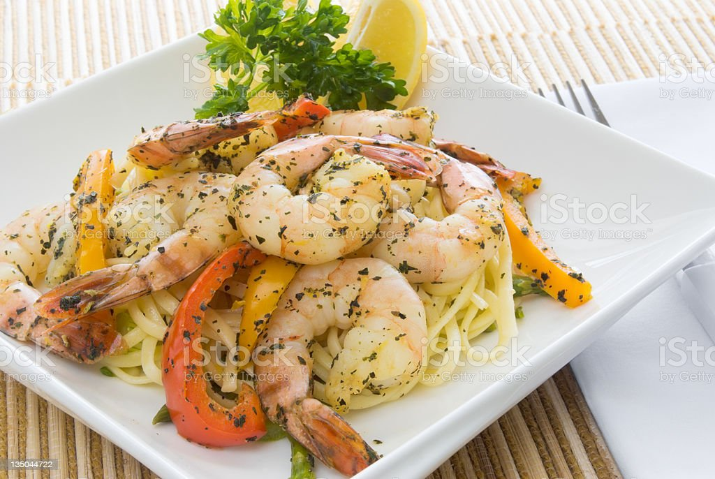 Cooked shrimp linguini meal served on a square white plate royalty-free stock photo