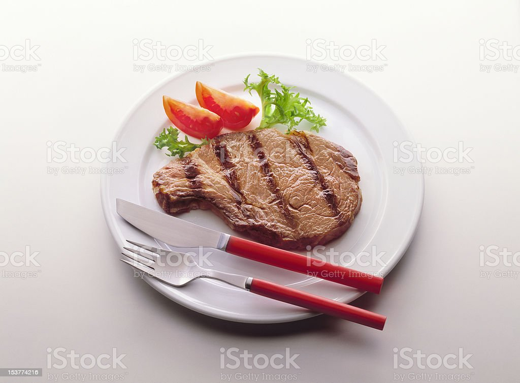 Cooked steak with tomato and escarole royalty-free stock photo