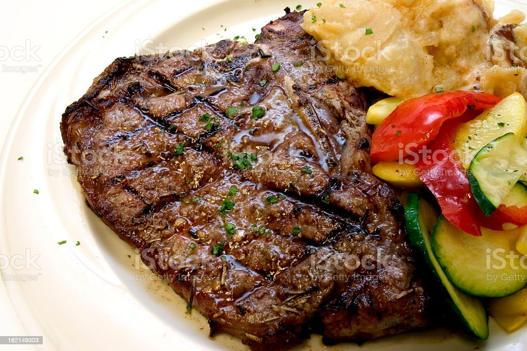 Cooked T-bone steak with grill marks on and vegetables stock photo