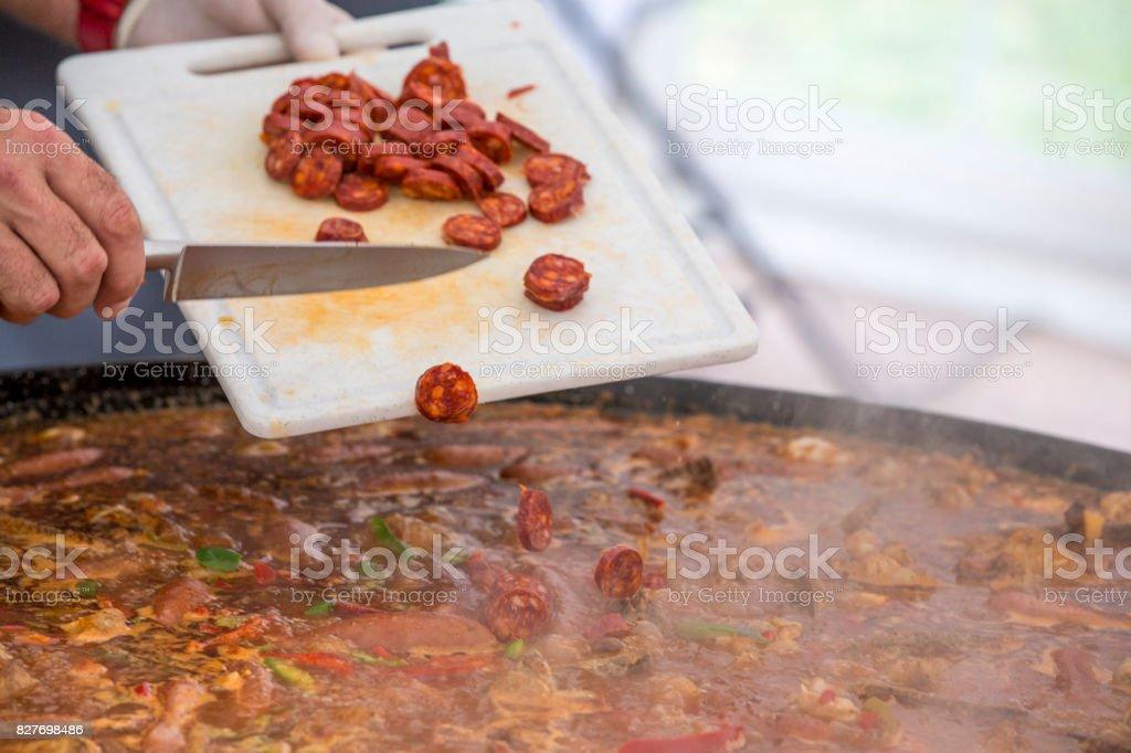 Cooker puts chorizo sausage pepperoni in paella jumbalaya stock photo