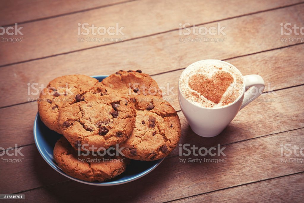 Cookie and cup of coffee on wooden table. stock photo