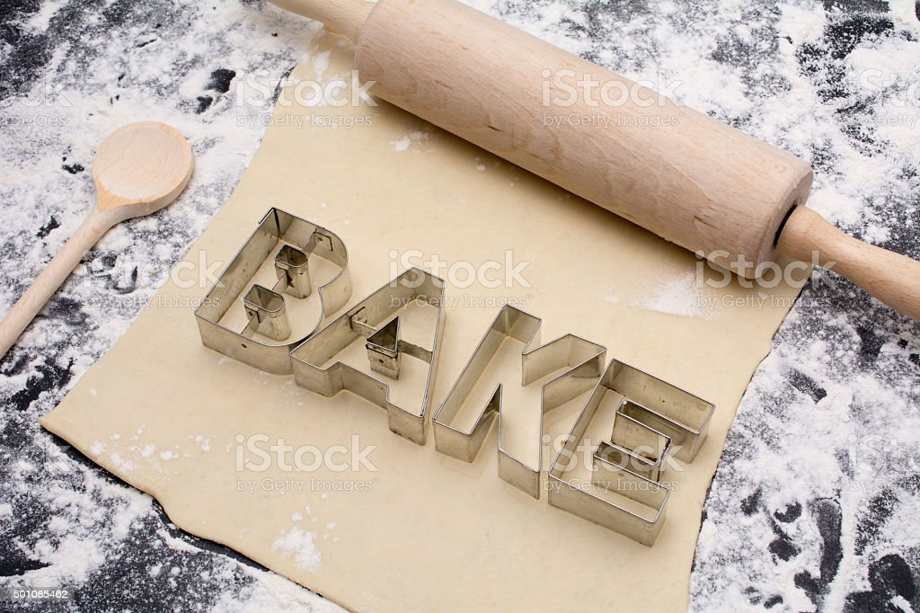 cookie cutters with word bake  on black counter with dough stock photo