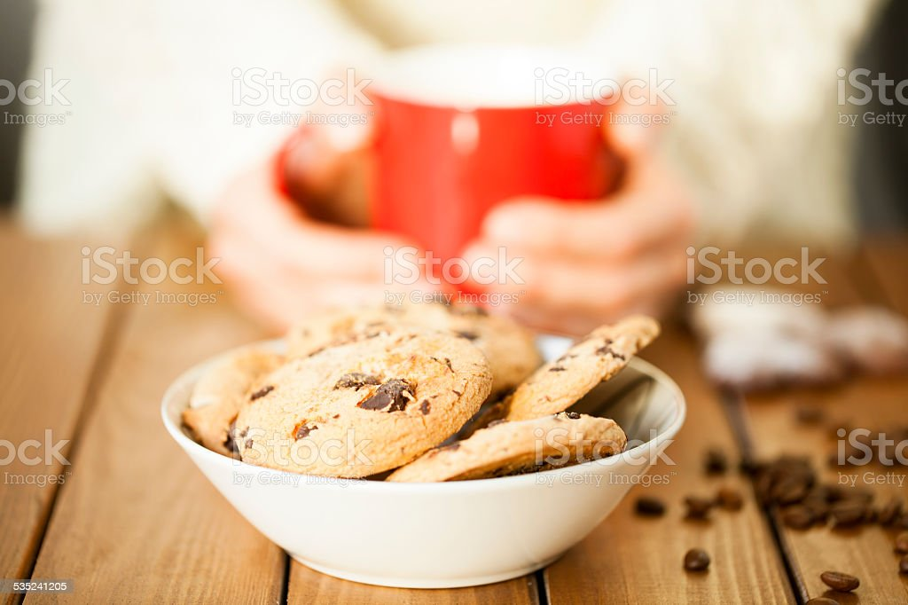Cookies and woman holding a cup stock photo