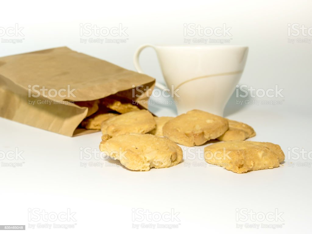 Cookies in paper bag and a cup of coffee stock photo