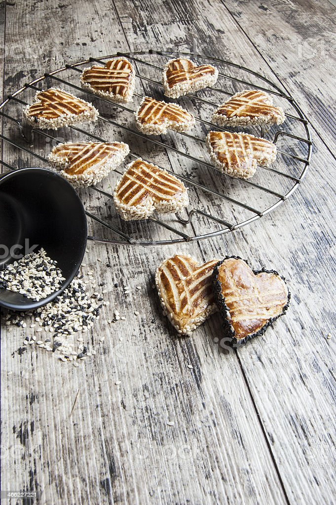 Cookies whith sesame in shape of heart on metal grille royalty-free stock photo