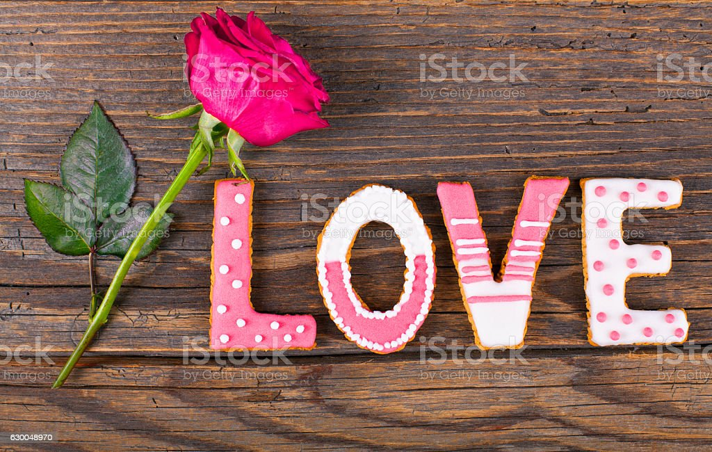 Cookies with love text in plate on rustic wooden table. stock photo