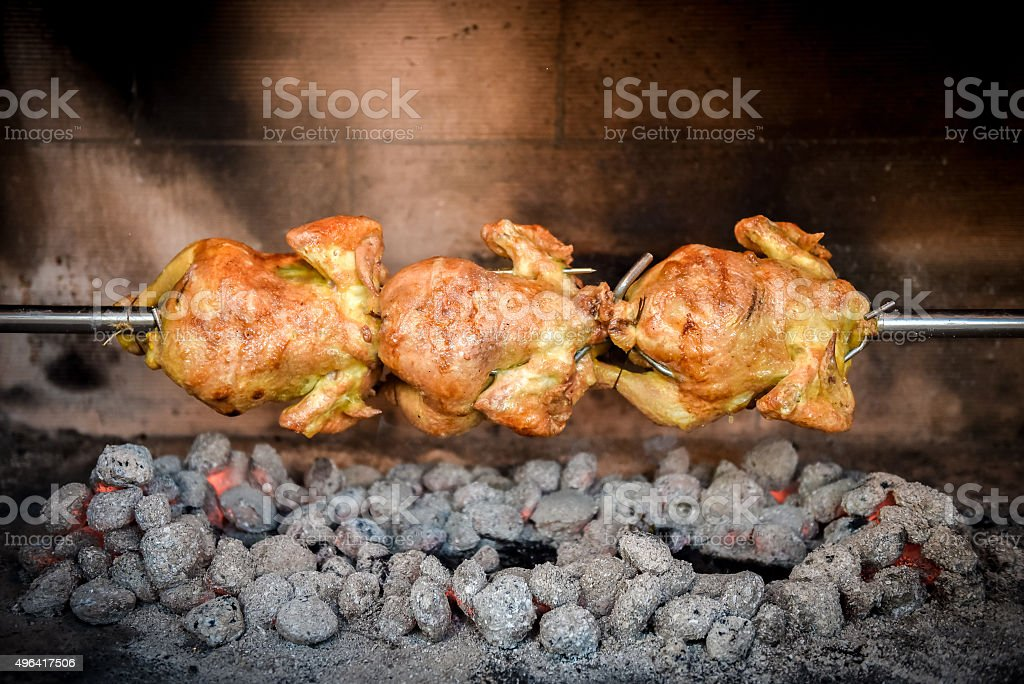 Cooking 3 rotisserie chicken on the grill with Charcoal stock photo