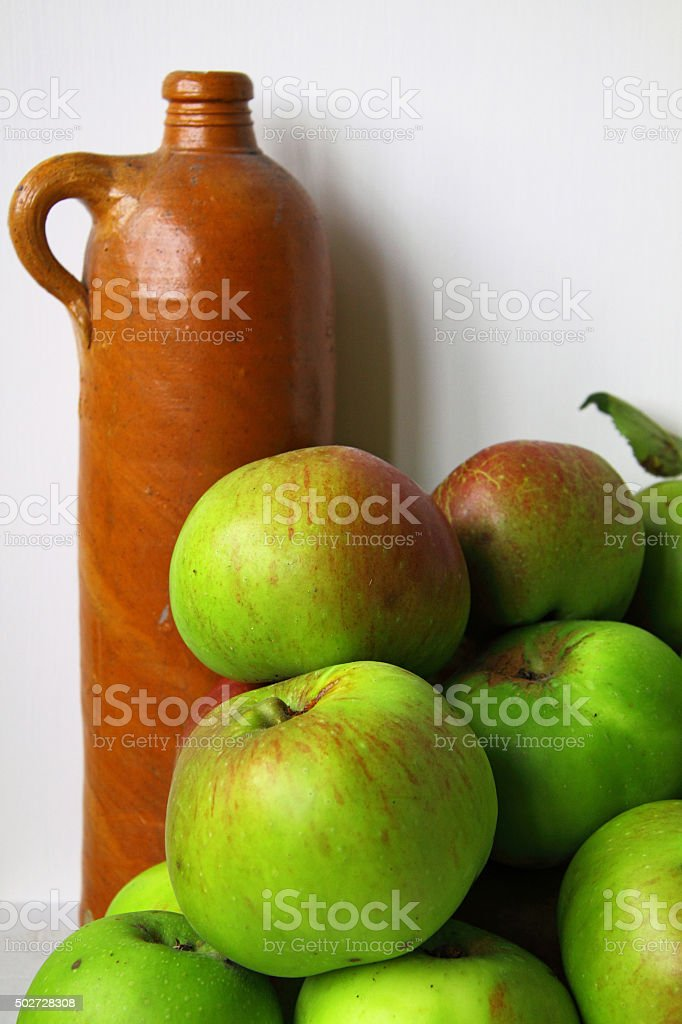 Cooking apples and stone bottle in a farmhouse kitchen stock photo
