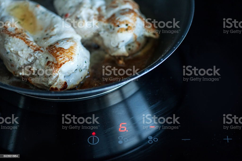 Cooking at home, chicken fillet with tomato, cooking pan, induction stock photo