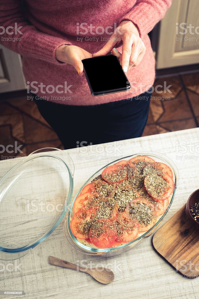 Cooking baked meat with vegetable from the internet recipe vertical stock photo