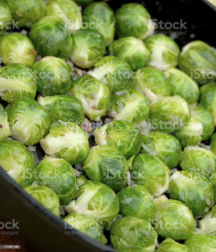 Cooking Brussels Sprouts: Vegetables Sauteeing, Cooked in Cast Iron Pan royalty-free stock photo