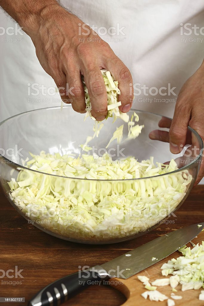Cooking Cabbage. Pressing cabbage with salt in glass bowl. royalty-free stock photo